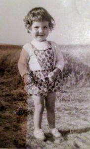 Über mich: Angela als kleines Kind am Strand von Juist.