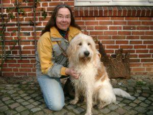 Der erste Hund aus dem Tierheim Sancho sitzt neben der knienden Autorin